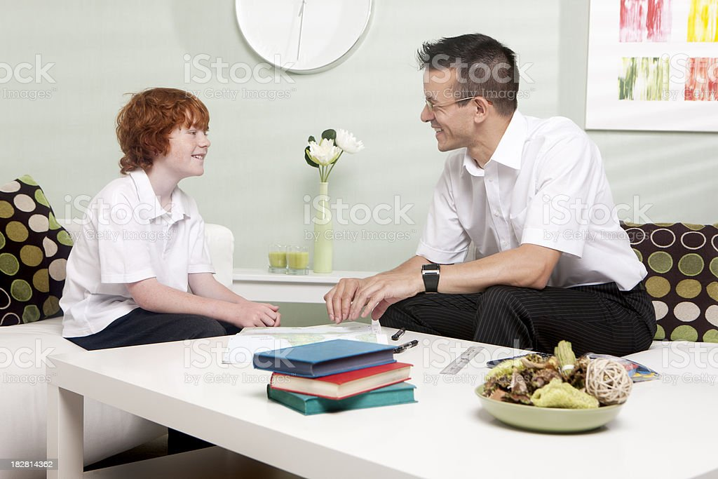 home tutor: teacher and schoolboy discussing progress royalty-free stock photo