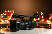 Home video camera in front Christmas lights  and presents in background. The scene is located in a studio environment. The footage is taken with Sony A7III camera