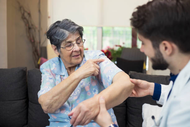 Home Visit Physiotherapist giving shoulder therapy to a senior woman arthritis stock pictures, royalty-free photos & images