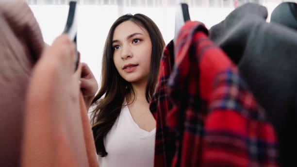 Haus Kleiderschrank oder Bekleidungsgeschäft Umkleideraum. Asiatische junge Frau wählen ihre Mode-Outfit-Kleidung im Schrank zu Hause oder im Geschäft. Mädchen denken, was Pullover zu tragen. – Foto
