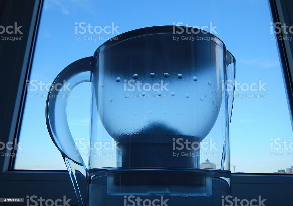 Home water filter with clear water on windowsill stock photo