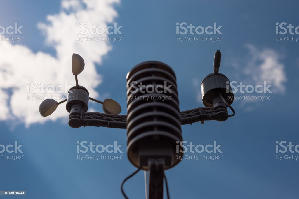 Home weather station on a background of blue sky with the sun behind the clouds. Measurement of temperature, humidity and wind direction stock photo