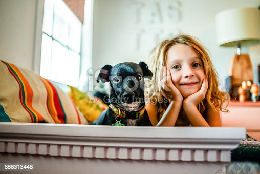 Little girl, 7 years old, cute and adorable, at home in a child's bedroom with her cute little pet dog, candid, casual, lifestyle