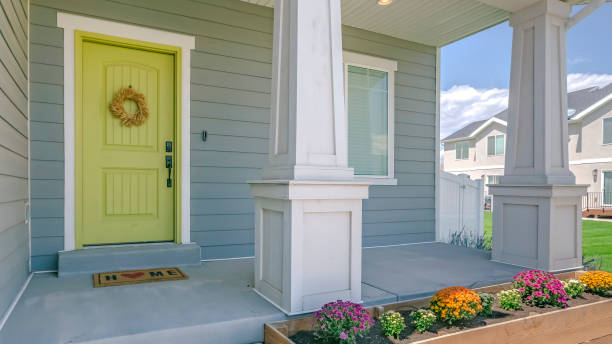 Home with porch and flowers in the garden Home with porch and flowers in the garden. Exterior view of a home with colorful flowers in the garden and stairs going to the porch. The yellow front door is decorated with a simple wreath. front door stock pictures, royalty-free photos & images