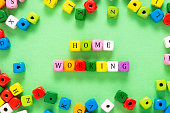 istock Home working inscription made from colorful wooden blocks over green background. Stay safe concept, home office, work from home. 1224016290