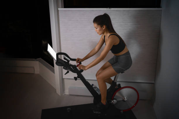Home workout indoor stationary bike Asian girl biking screen with online classes woman training on smart fitness equipment indoors for cycling exercise. Late at night in bedroom stock photo