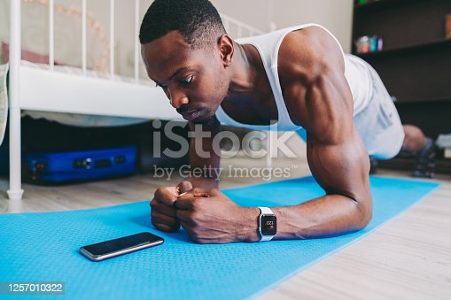 African American sportsman exercising planks at home, using exercise timer on smartphone