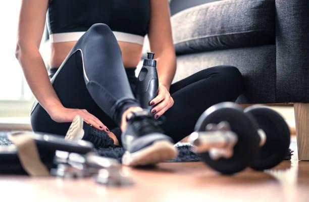 Heimtraining, Krafttraining und Fitness-Trainingskonzept. Frau in Sportbekleidung im Wohnzimmer mit Fitness-Ausrüstung und Hantel hält Wasserflasche. Gesunder sportlicher Lebensstil. – Foto