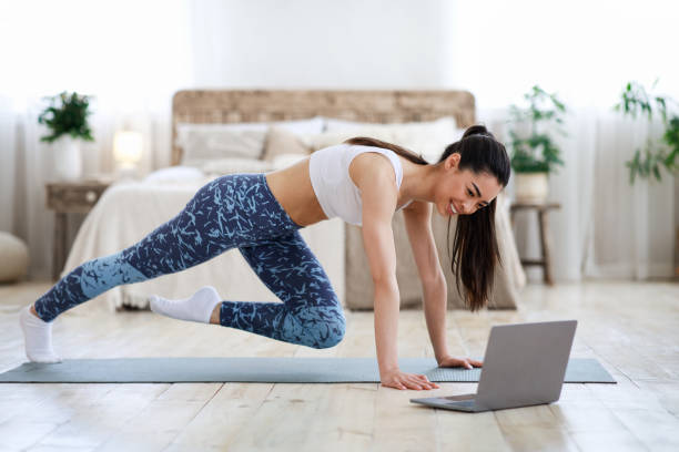 home workout. young asian girl practicing sport in front of laptop - young girl computer home front imagens e fotografias de stock