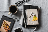 istock Home workplace with a business, education, education accessories. Notepad, tablet, phone, earbuds, pen, glasses, coffee on grey background, top view. Flat lay 858655100