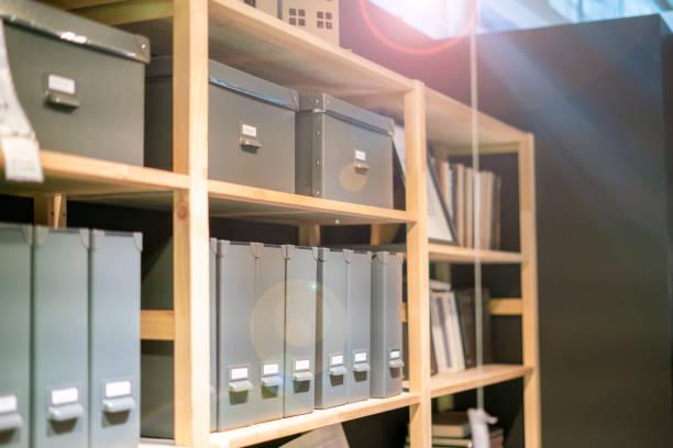 heimat-werkstatt mit büchern und anderen papieren auf dem rack regal und in der kiste v - uhrenhalter stock-fotos und bilder