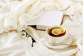home workspace in bed concept. tea with lemon, knitted sweater , glasses and book. warm beige pastel colors lifestyle autumn winter composition.   copy space.