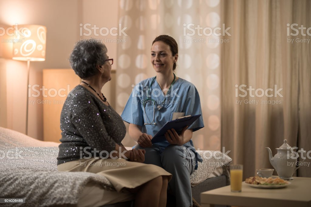 Homecare nurse sitting and talking with senior women in her bedroom