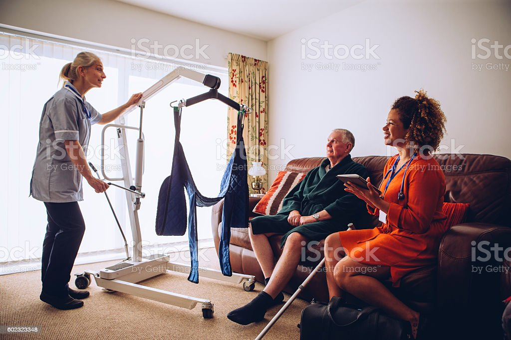 Homecare Workers preparing Hoist stock photo