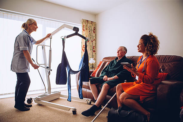Homecare Workers preparing Hoist Two homecare nurses at an elderly mans house. They have a hoist set up. retrieving stock pictures, royalty-free photos & images