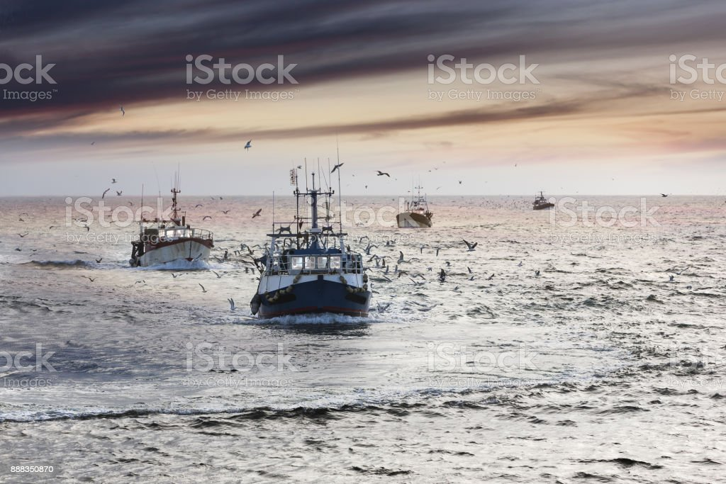 Homecoming: Tired fishermans ships approaching after a hard day, Le Guilvinec,Brittany, France stock photo
