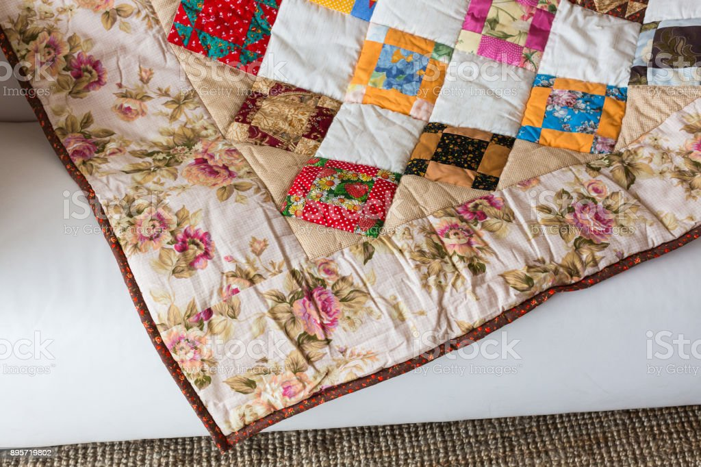 homecraft, art, vintage concept. front view on a quilted blanket with square and triangle pattnern and colorfull print consist of roses, poppy and other types of plants stock photo