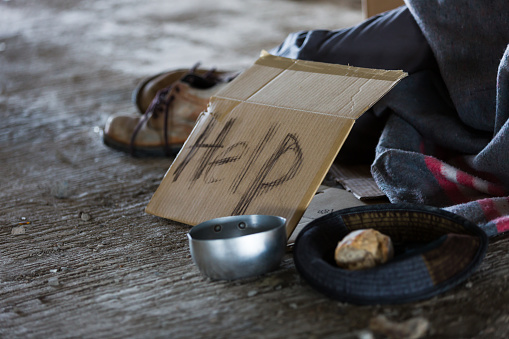 Homeless and hungry man sleeping at abandoned building or on street with signboard for help and need food and money