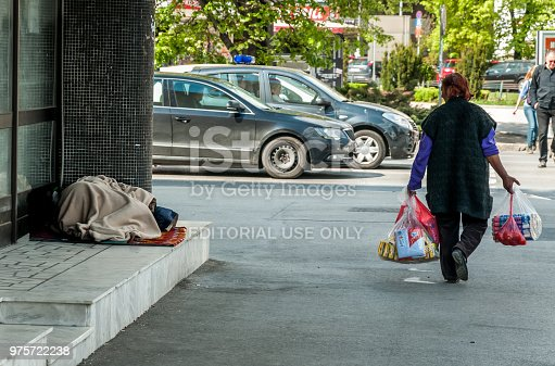 istock Homeless barefooted woman sleep on the urban street in the city on the sidewalk near the building while people are passing by, selective focus. 975722238