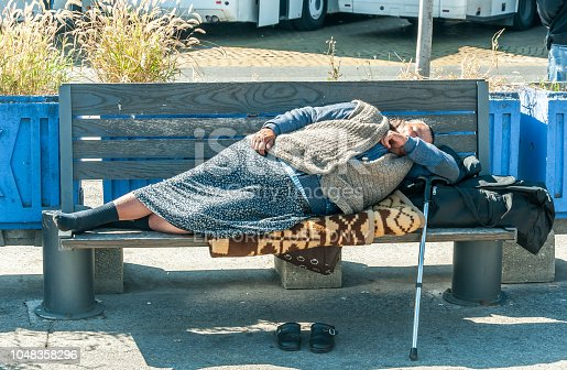 istock Homeless barefooted woman sleep on the wooden bench on urban street in the city on the sidewalk 1048358296