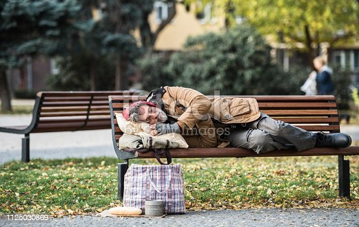 A homeless beggar man with a bag lying on bench outdoors in city, sleeping. Copy space.