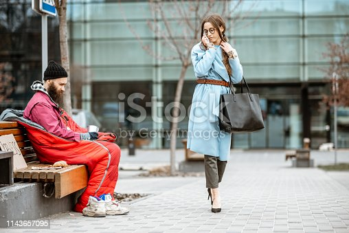 Homeless begging money while sitting on the bench with passing by businesswoman near the business center