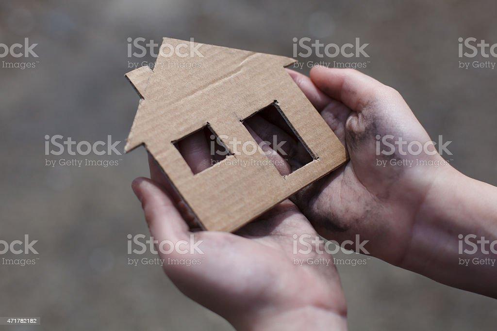 Sans-abri garçon tenant un carton house photo libre de droits