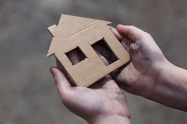 homeless boy holding a cardboard house - homelessness stock photos and pictures