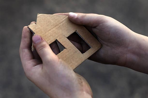 homeless boy holding a cardboard house stock photo