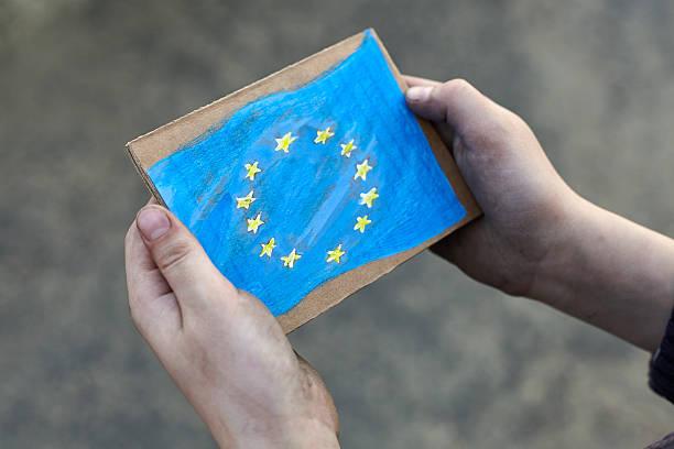 homeless boy holding European Union flag stock photo
