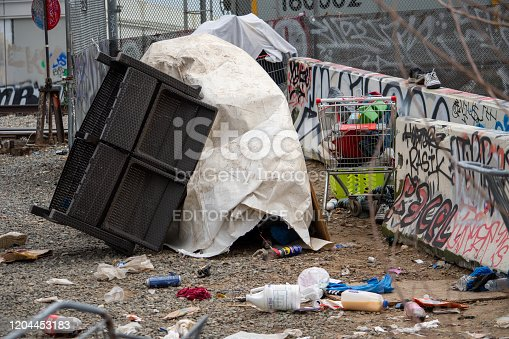458464131istockphoto A homeless camp stands adjacent to trash and debris near 8100 Haskell Ave, by railroad tracks. 1204453183