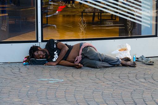 Homeless dark-skinned man is sleeping on street of Paris, France