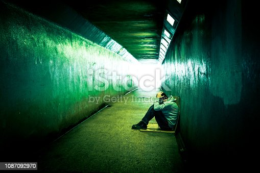 Color image depicting a young homeless man sitting alone in a cold, dark subway tunnel. The man is clearly sad, and has an unkempt beard. He sits with his back to the wall of the tunnel while the diminishing perspective of the subway tunnel recedes into the distance.