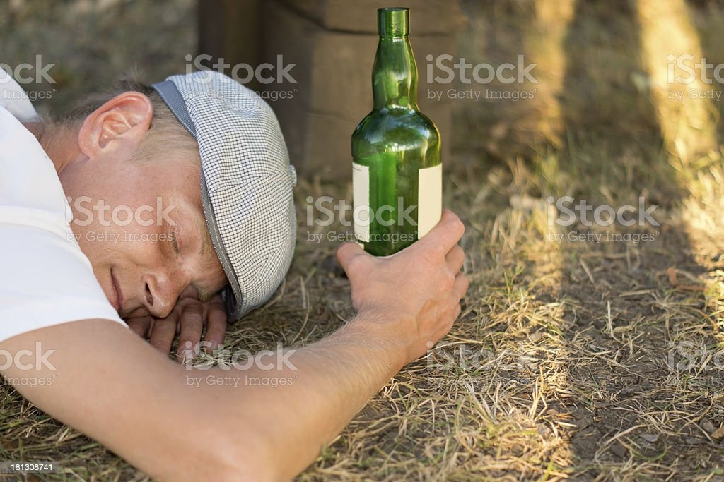 Homeless drunk adult man sleeping on the ground royalty-free stock photo