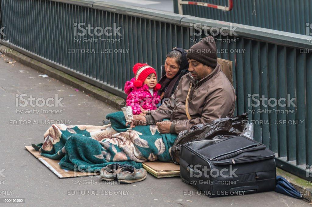 Homeless family sitting on the street stock photo
