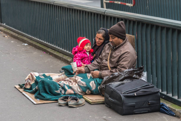 homeless family sitting on the street - homelessness stock pictures, royalty-free photos & images