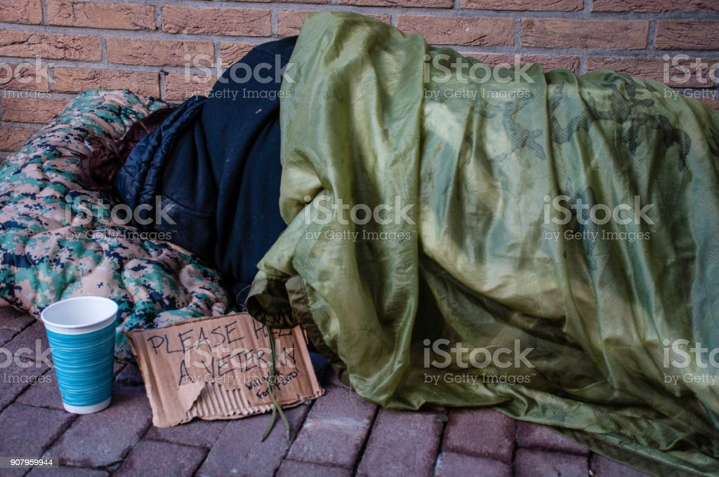 Homeless Female Veteran Sleeping Against Brick Building stock photo
