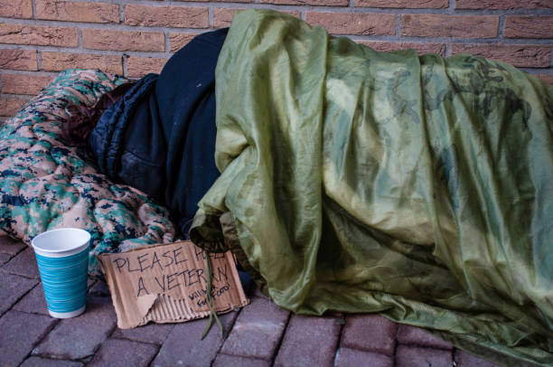 homeless female veteran sleeping against brick building - homelessness stock photos and pictures
