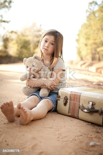 istock Homeless Girl Hugging Teddy Bear by Suitcase on Dirt Road 540599776