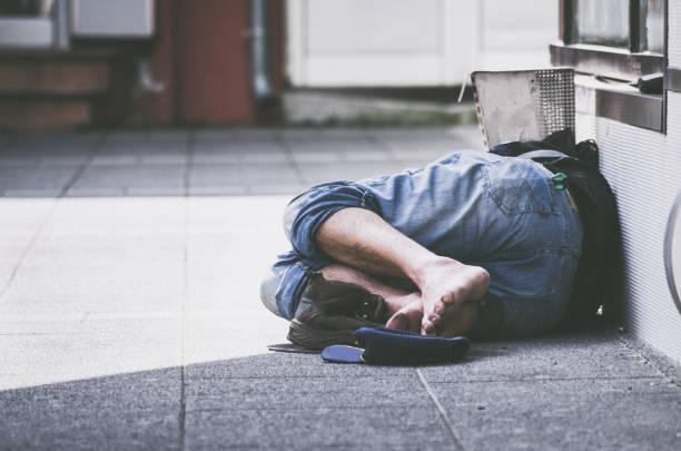 obdachlos. obdachloser schläft auf der straße, im schatten des gebäudes. soziale dokumentarfilm. - dokumentation stock-fotos und bilder