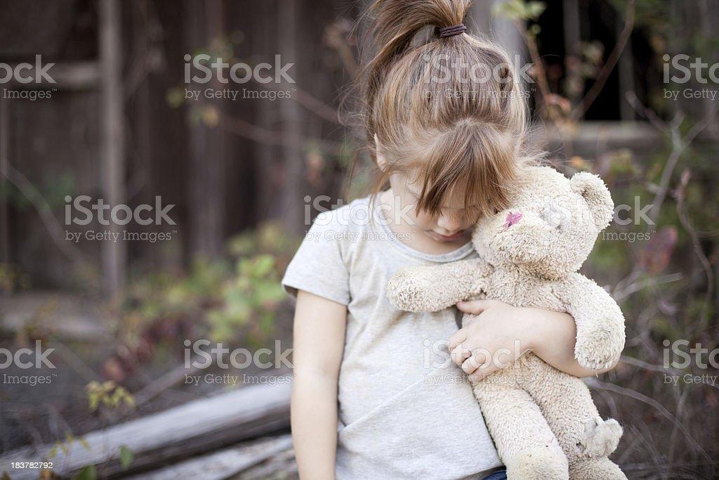 Homeless Little Girl Holding Old, Raggedy Teddy Bear stock photo