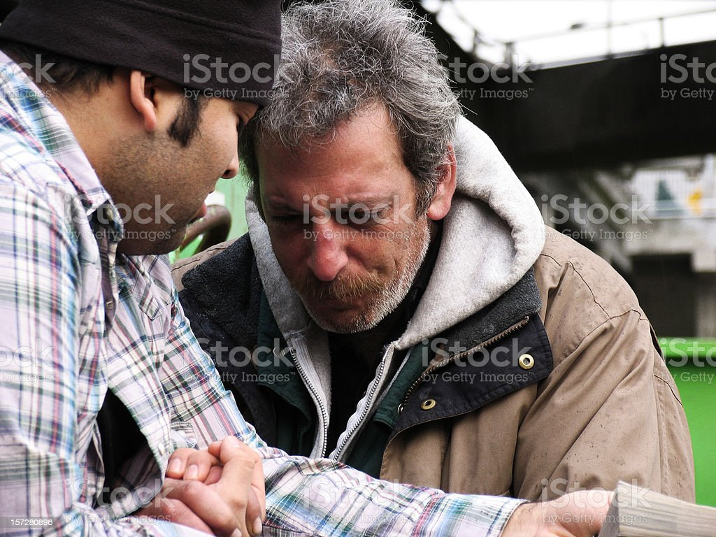 Homeless Male Crying with Listening to Scripture stock photo