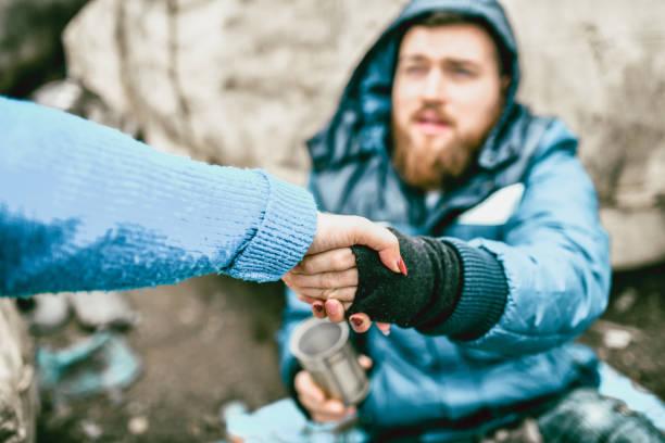homem desabrigado na rua que começ a ajuda da fêmea - sem teto - fotografias e filmes do acervo