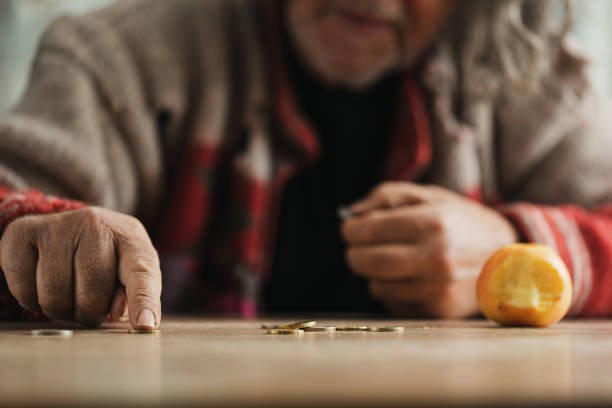 Homeless man counting coins stock photo