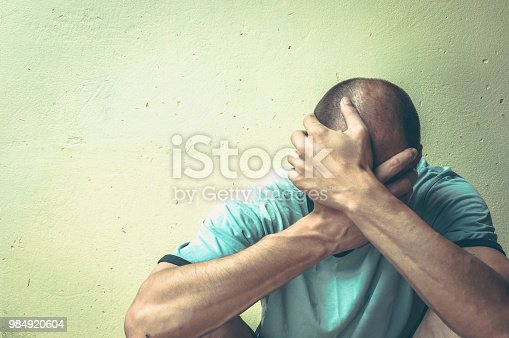 istock Homeless man drug and alcohol addict sitting alone and depressed on the street in the shadow feeling anxious and lonely, social documentary concept 984920604