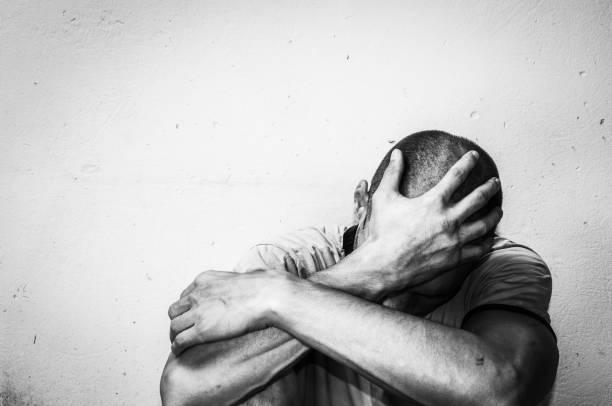 obdachloser drogen- und alkoholmissbrauch addict sitzt einsam und depressiv auf der straße, die angstgefühle und einsam, soziale dokumentarische konzept schwarz und weiß - depression stock-fotos und bilder