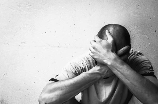 senzatetto tossicodipendente e tossicodipendente di alcol seduto da solo e depresso per strada sentendosi ansioso e solo, concetto di documentario sociale in bianco e nero - assuefazione foto e immagini stock
