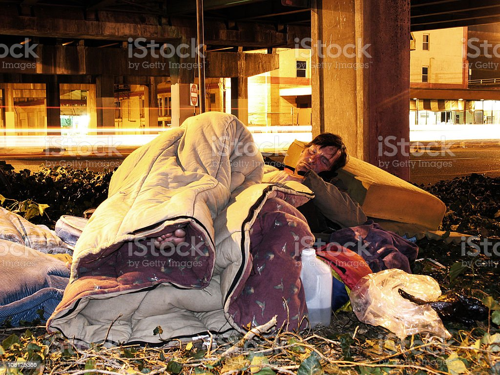 Homeless Man Falling Asleep by the Road stock photo