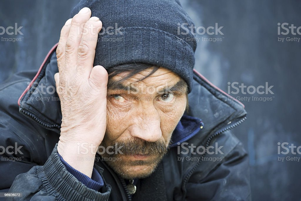 A homeless man holding his hand to his head on a city street royalty-free stock photo