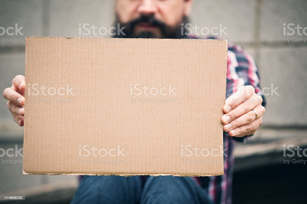 Homeless Man Holding Out A Blank Cardboard Sign stock photo
